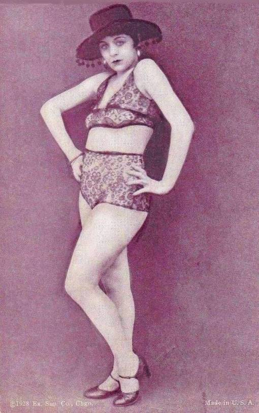 arcade-card-exhibit-supply-company-pin-up-woman-standing-with-hands-on-hips-wearing-spanish-hat-and-lace-two-piece-outfit-1928