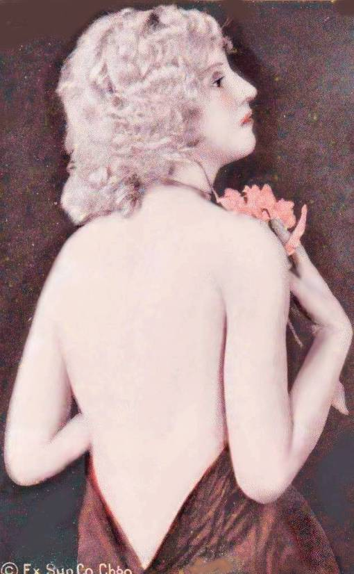 A ARCADE CARD - EXHIBIT SUPPLY COMPANY - PIN-UP - BLONDE WOMAN WITH BACK TO CAMERA AND HEAD PROFILE HOLDING CORSAGE - 1920s
