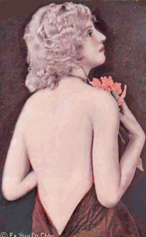 a-arcade-card-exhibit-supply-company-pin-up-blonde-woman-with-back-to-camera-and-head-profile-holding-corsage-1920s