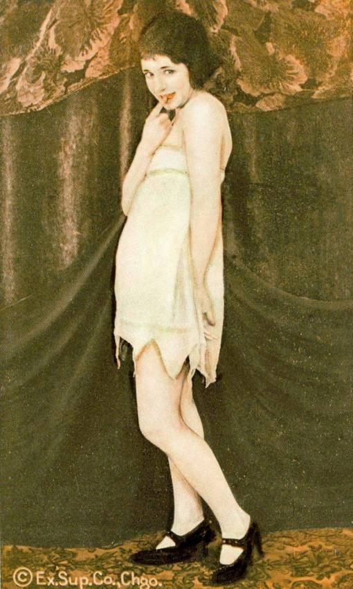 A ARCADE CARD - EXHIBIT SUPPLY COMPANY - PIN -UP - WOMAN IN BOBBED HAIR STANDING IN NIGHTIE WITH FINGER ON LIPS - 1920s