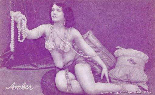 A ARCADE CARD - EXHIBIT SUPPLY COMPANY - PIN-UP - WOMAN SITTING DRAPPED WITH PEARLS LOOKING UP - CALLED AMBER - 1928
