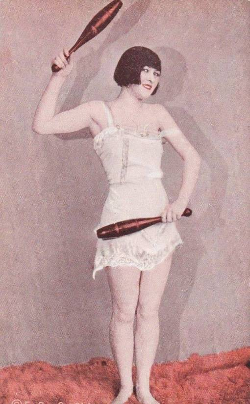 A ARCADE CARD - EXHIBIT SUPPLY COMPANY - PIN-UP - WOMAN WITH BOBBED HAIR AND NIGHTIE HOLDING INDIAN CLUBS - 1920s