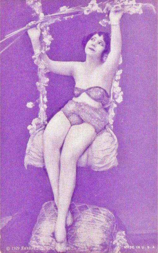 A ARCADE CARD - EXHIBIT SUPPLY COMPANY - PIN-UP - WOMAN WITH BOBBED HAIR ON FLORAL SWING WITH WHIMSICAL FACE - 1929