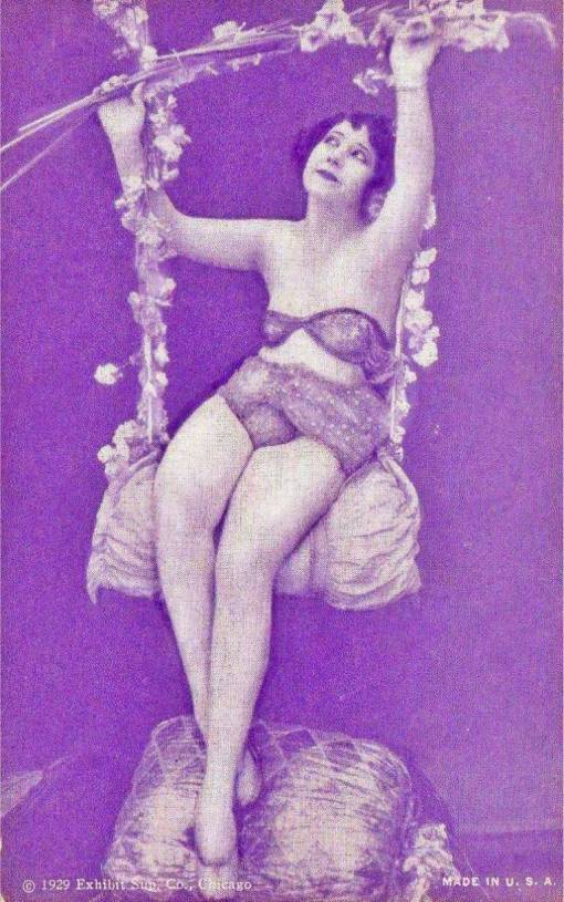 a-arcade-card-exhibit-supply-company-pin-up-woman-with-bobbed-hair-on-floral-swing-with-whimsical-face-19291