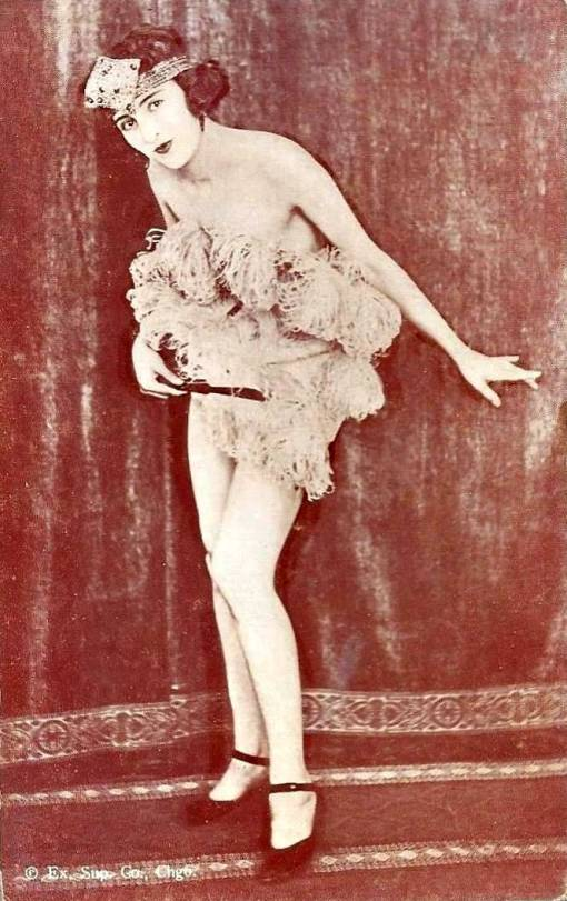 arcade-card-exhibit-supply-company-pin-up-woman-standing-with-bobbed-hair-and-head-band-covering-herself-with-large-feather-fan-1920s