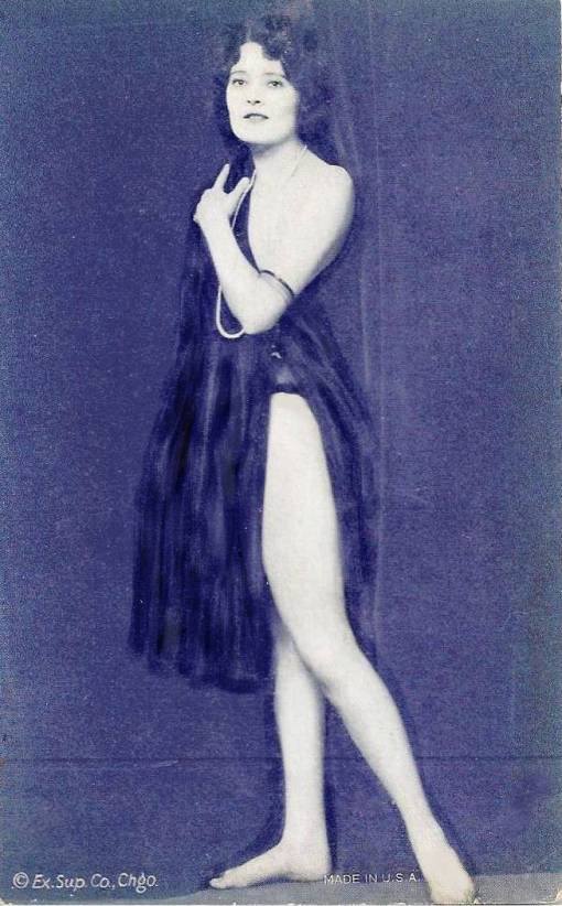 ARCADE CARD - EXHIBIT SUPPLY COMPANY - WOMAN STANDING PROFILE WITH ONE LEG STRETCHED TO SIDE LOOKING AT CAMERA IN FILMY NIGHTIE - 1920s