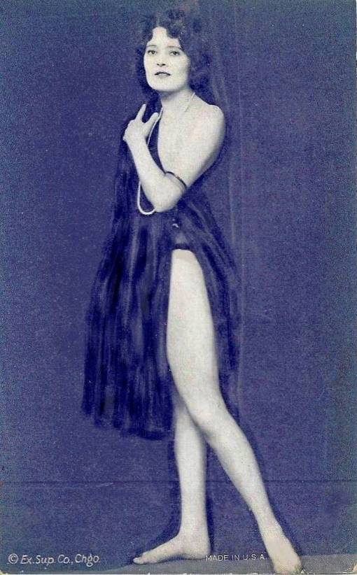 arcade-card-exhibit-supply-company-woman-standing-profile-with-one-leg-stretched-to-side-looking-at-camera-in-filmy-nightie-1920s