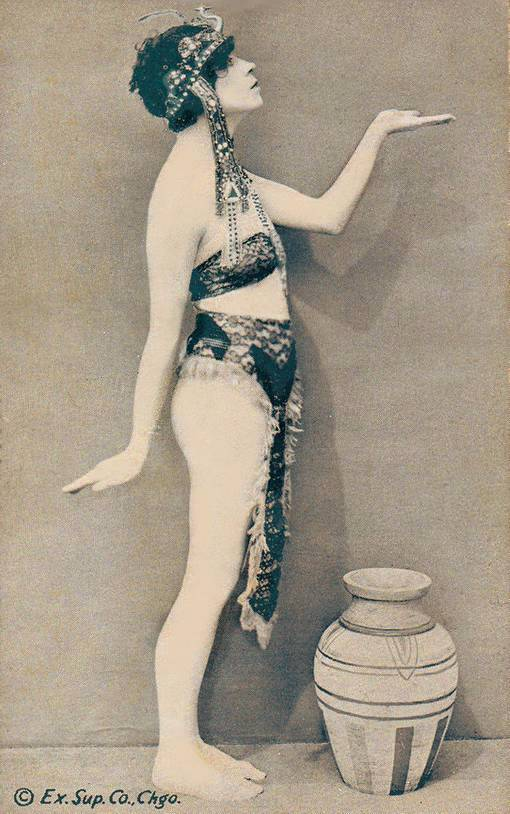 A ARCADE CARD - EXHIBIT SUPPLY COMPANY - PIN-UP - WOMAN STANDING PROFILE IN EGYPTIAN -LIKE POSE AND HEAD DRESS - 1920s