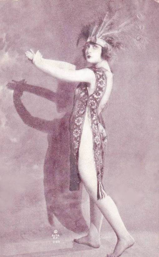 arc ARCADE CARD - ALTA - PIN-UP - WOMAN STANDING IN PEACOCK-FEATHER HEADDRESS AND SHEER NIGHTIE MAKING SHADOW IMAGE WITH HANDS - c1920