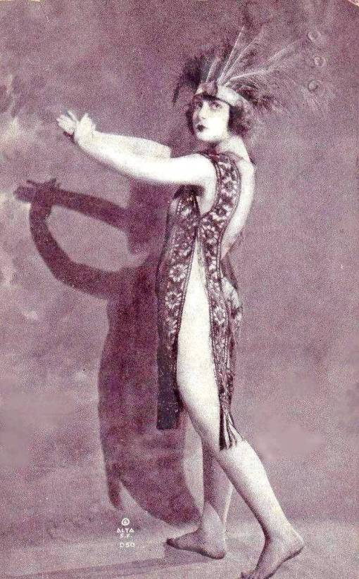 arc-arcade-card-alta-pin-up-woman-standing-in-peacock-feather-headdress-and-sheer-nightie-making-shadow-image-with-hands-c1920