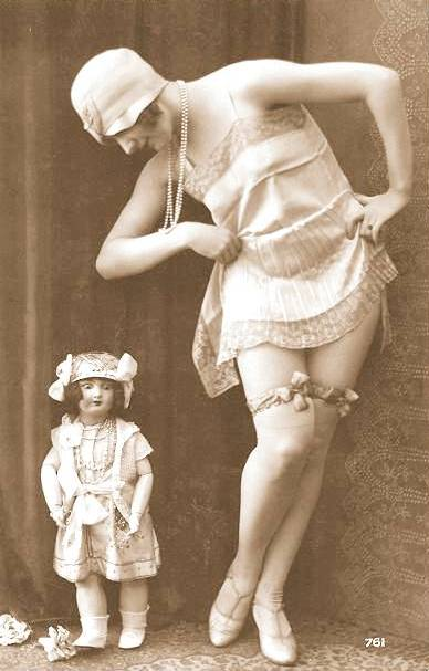 arc ARCADE CARD - FRENCH - WOMAN IN CLOCHE HAT STANDING NEXT TO BOUDOIR DOLL WITH SLIP HIKED - 1920s