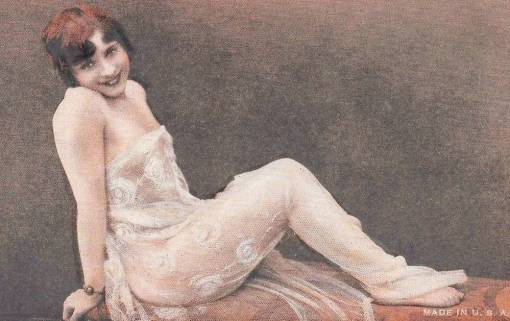 arc ARCADE CARD - LIKELY EXHIBIT SUPPLY COMPANY - PIN-UP - WOMAN WITH BOBBED HAIR WRAPPED IN LACE THROW LEANING BACK ON LOUNGE - 1920s