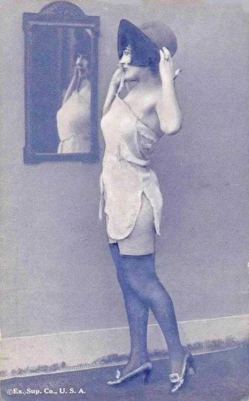 arc ARCADE CARD - EXHIBIT SUPPLY COMPANY - PIN-UP - WOMAN STANDING PROFILE IN NIGHTIE AND HAT LOOKING INTO WALL MIRROR - 1920s