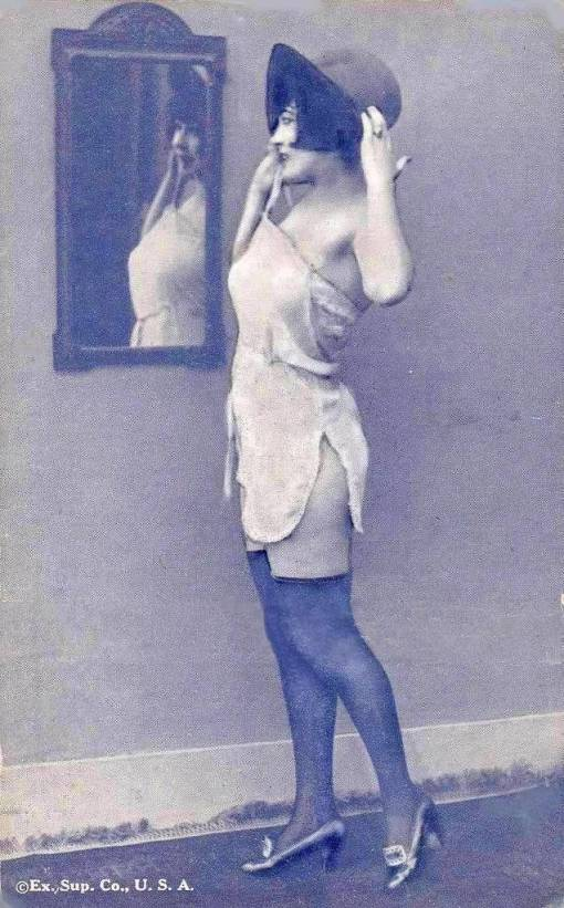 arc-arcade-card-exhibit-supply-company-pin-up-woman-standing-profile-in-nightie-and-hat-looking-into-wall-mirror-1920s