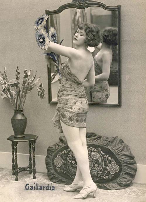 arc ARCADE CARD - FRENCH - PIN-UP - WOMAN WITH BOBBED HAIUR STANDING IN SILKY WRAP LOOKING AT FLOWERS SHE HOLDS - 1920s