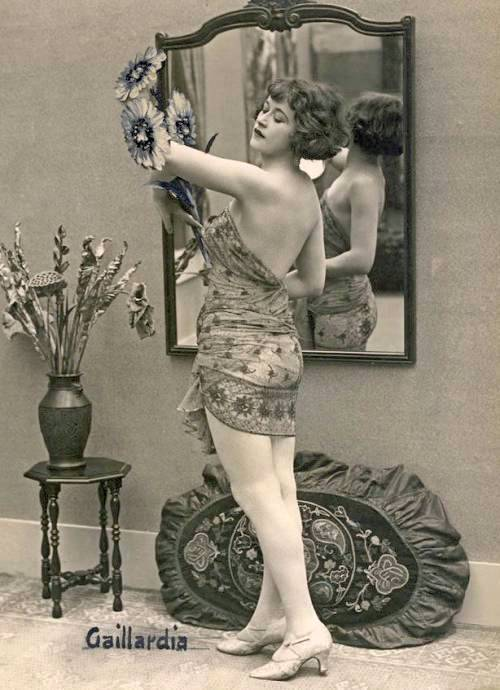 arc-arcade-card-french-pin-up-woman-with-bobbed-haiur-standing-in-silky-wrap-looking-at-flowers-she-holds-1920s
