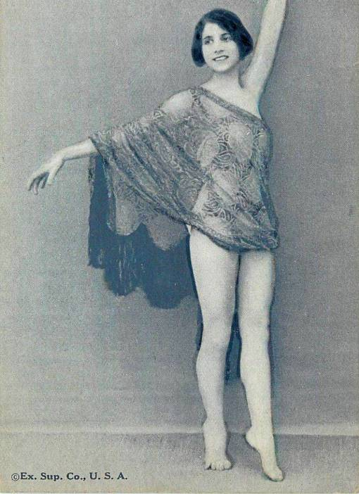 A ARCADE CARD - EXHIBIT SUPPLY COMPANY - PIN-UP - WOMAN STANDING WITH ARMS OUTSTRETCHED IN SHEER WRAP - 1920s