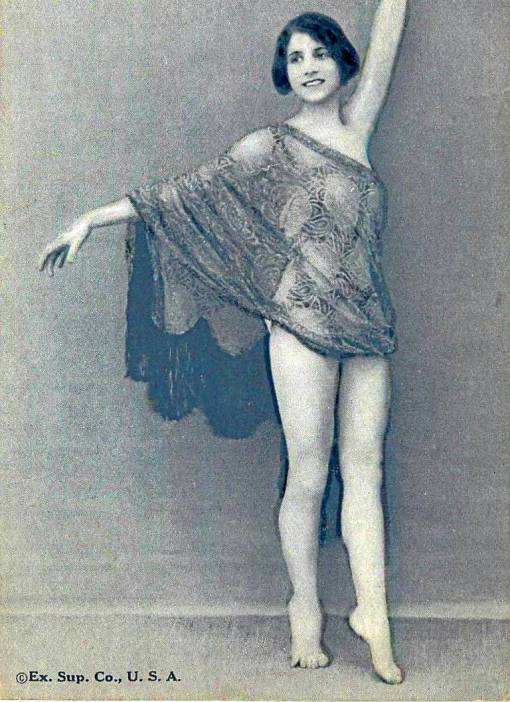 a-arcade-card-exhibit-supply-company-pin-up-woman-standing-with-arms-outstretched-in-sheer-wrap-1920s
