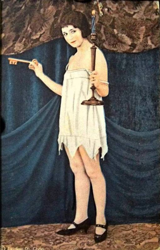 aa-arcade-card-exhibit-supply-company-pin-up-woman-with-bobbed-hair-standing-in-nightie-and-key-and-candle-tinted-series-1920s
