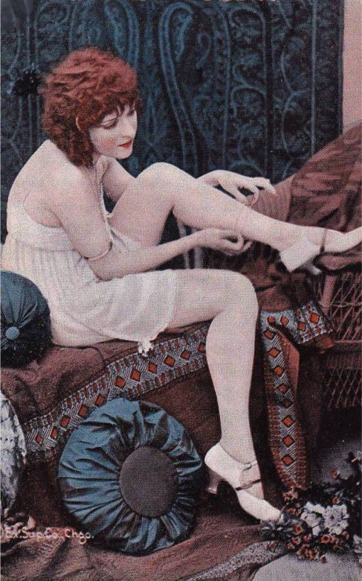 A ARCADE CARD - EXHIBIT SUPPLY COMPANY - RED-HAIRED WOMAN IN NIGHTIE SITTING ON A BED ADJUSTING HER STOCKING - TINTED SERIES - 1920s