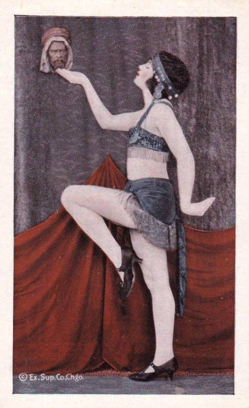 A ARCADE CARD - EXHIBIT SUPPLY COMPANY - WOMAN MARCHING PROFILE HOLDING UP A SMALL HEAD IN ONE HAND - TINTED SERIES - 1920s