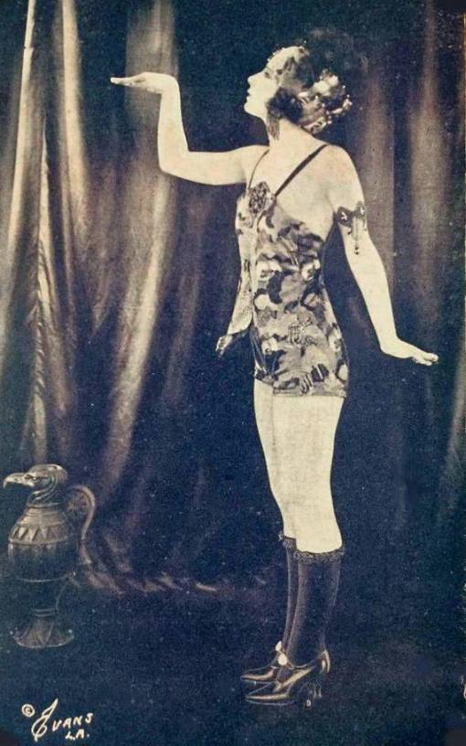 ARCADE CARD - EVANS L A - PIN-UP - WOMAN PROFILE IN EGYPTIAN-LIKE POSE WEARING FLORAL PATTERN BATHING SUIT AND SHOES AND LONG STOCKINGS - 1920s