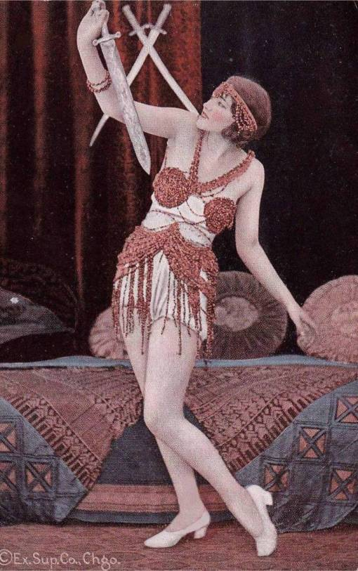 ARCADE CARD - EXHIBIT SUPPLY COMPANY - PIN-UP - WOMAN IN GRACEFUL DANCE POSE WITHA SWORD AND BEADED OUTFIT - ELABORATE BED BEHIND - TINTED SERIES - 1920s