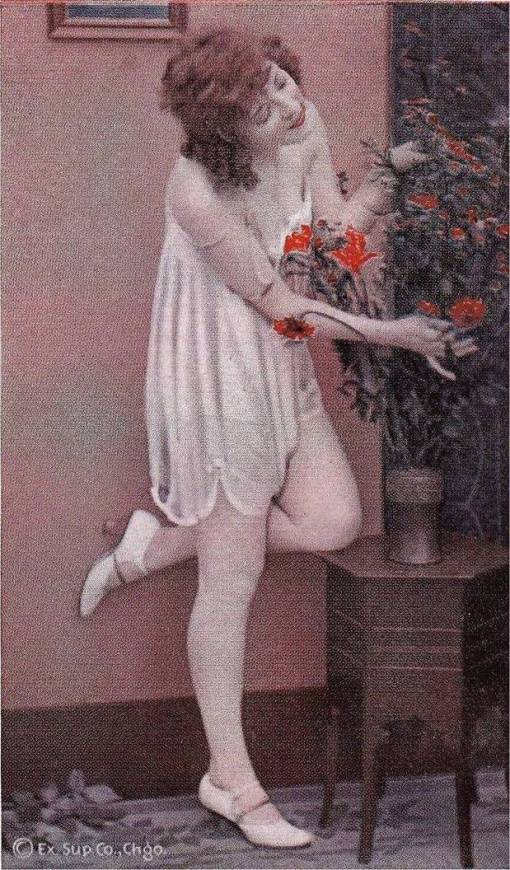 ARCADE CARD - EXHIBIT SUPPLY COMPANY - PIN-UP - WOMAN WEARING NIGHTIE AND HIGH HEELS WITH ONE FOOT AGAINST WALL ARRANGING VASE OF FLOWERS - TINTED SERIES - 1920s