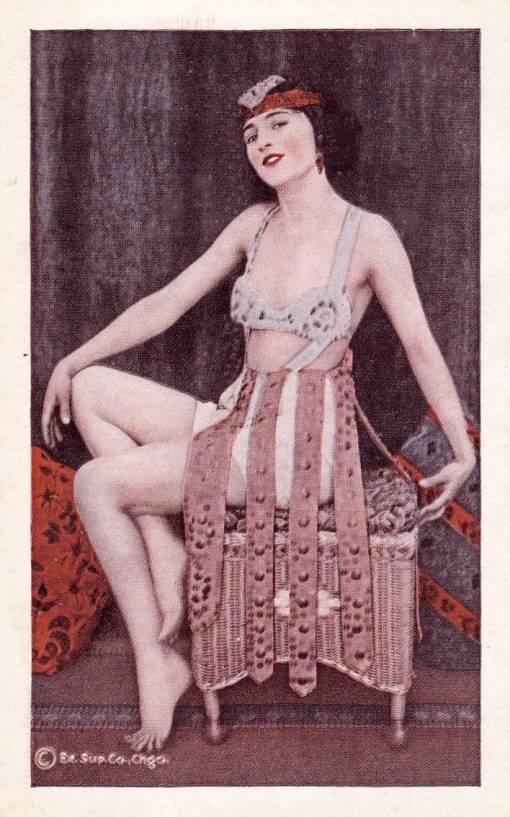 ARCADE CARD - EXHIBIT SUPPLY COMPANY - WOMAN SITTING SIDEWAYS ON HASSOCK POSED GRACEFULLY IN ODD ROMANESQUE COSTUME - TINTED SERIES - 1920s