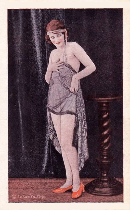 ARCADE CARD - EXHIBIT SUPPLY COMPANY - WOMAN WITH HEADBAND AND TASSELS HOLDING SHEER WRAP AROUND HER AND COY LOOK TO OUR RIGHT - TINTED SERIES - 1920s