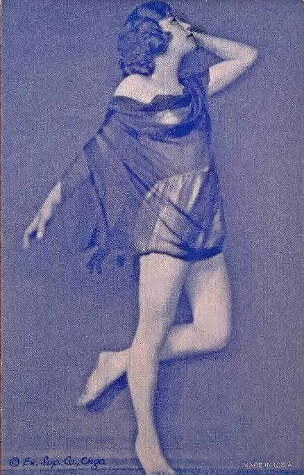 A ARCADE CARD - CHICAGO EXHIBIT SUPPLY - WOMAN STANDING ON ONE FOOT PROFILE WITH A BIT OF VEIL OVER TWO-PIECE SHINY OUTFIT - GRACEFUL POSE - BEAUTIFUL PROFILE - PURPLE TINT- 1920s
