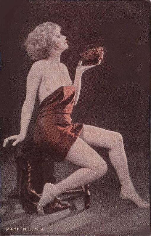 A ARCADE CARD - EXHIBIT SUPPLY COMPANY - PIN-UP - BLONDE WOMAN IN A WRAP SITTING PROFILE ON A STOOL HOLDING OUT A LITTLE BASKET - TINTED -1920s