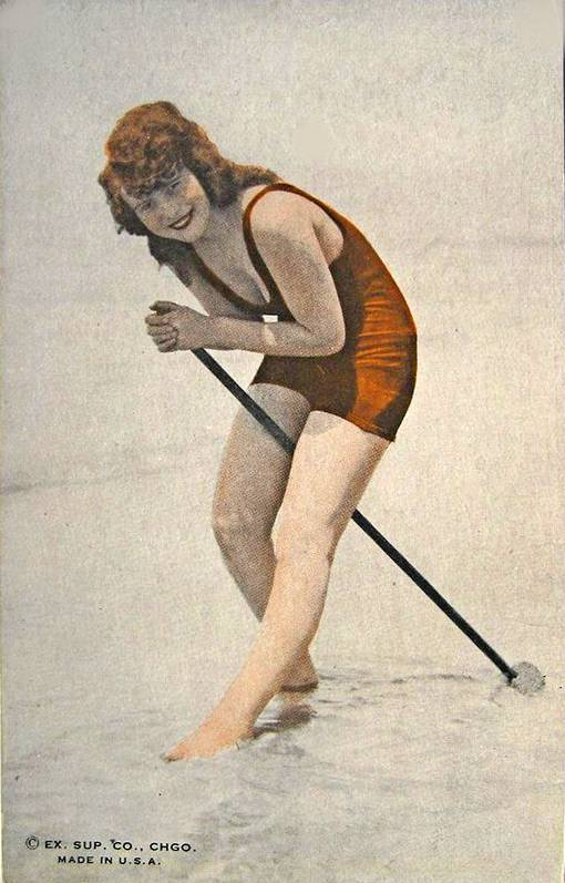 ARCADE CARD - EXHIBIT SUPPLY COMPANY - RED-HAIRED WOMAN STANDING IN SHALLOW WATER WITH A TOOL WEARING RED WOOLLY BATHING SUIT - TINTED - 1920s